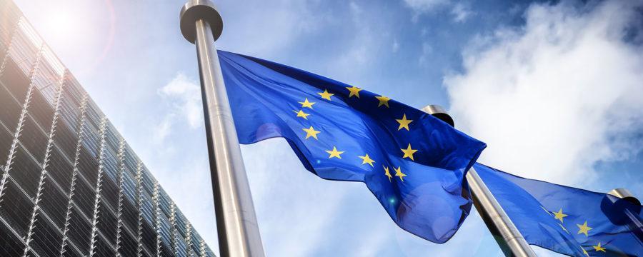 Två EU flaggor hissade mot blå himmel